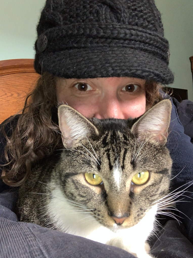 A woman in a black knitted hat with curly hair hides behind a tabby cat. Only her eyes and the top part of her nose are visible. She appears to smile.